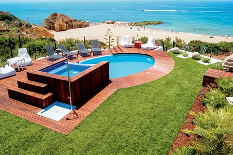 An open garden and pool area overlook a golden, sandy beach in the Algarve