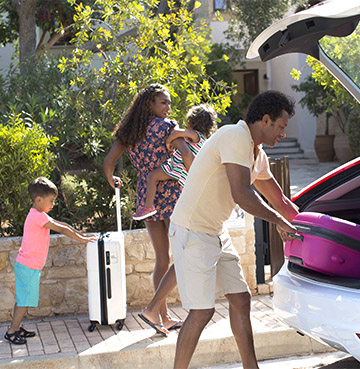Family unloading their hire car at their villa
