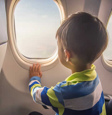 A young boy looks out of a plane window