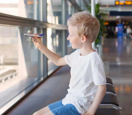 A boy at the airport playing with a toy plane