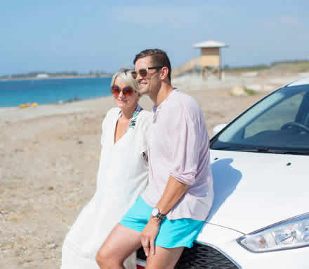 A couple perched on their car at the beach