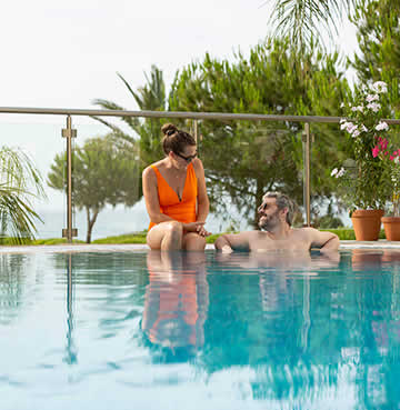 A couple relax in their villa's private swimming pool