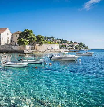 Crystal-clear, aquamarine waters in Hvar are backed by a traditional fishing village and bobbing boats