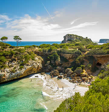 Craggy cliffs cocoon a beautiful, hidden bay in Mallorca