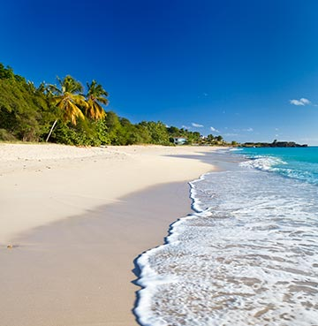 Gentle waves lap the white-powder sands at Half Moon Bay, Antigua