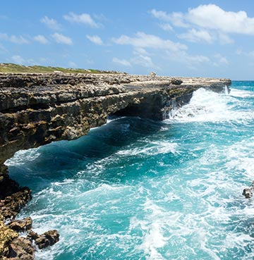 Rugged and wild waves crash against the Devil's Bridge, Antigua