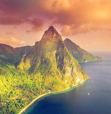 An aerial view of the iconic volcanic plus, The Pitons, at sunset. The sky glows pink and orange and luscious rainforest spreads out across the island.