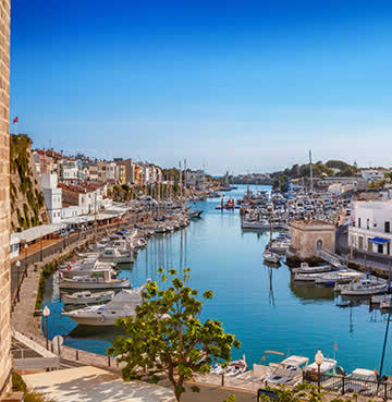 Yachts moored along elegant riverside in Ciutadella, Menorca