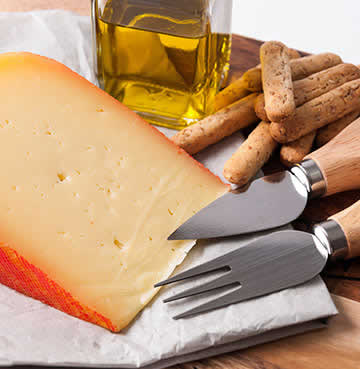 Mahon cheese on chopping board with utensils