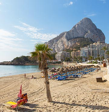 Golden Costa Blanca beach looking toward the Penon de Ifach rock