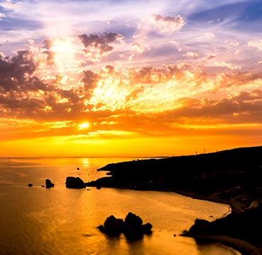 A serene sunset over Aphrodite's Rock and Beach.