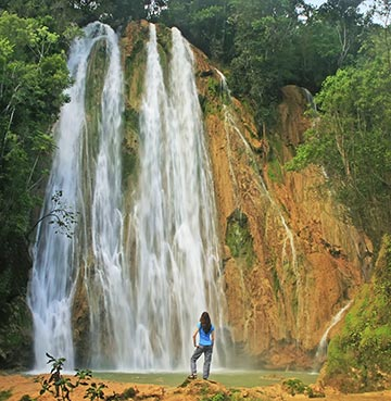 Woman stands looking up at the beautiful Salto El Limón waterfall, Dominican Republic