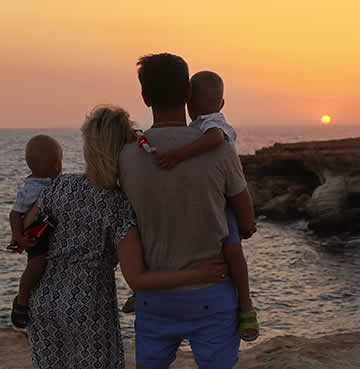A young mother and father watch the sunset with their two toddlers