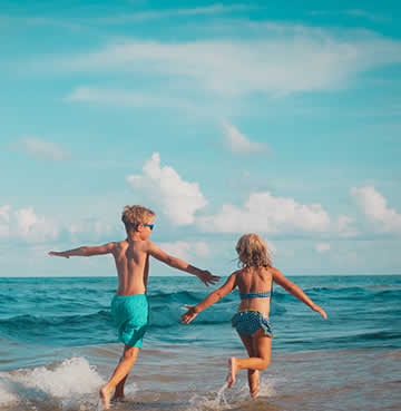 Two young children run into the sea